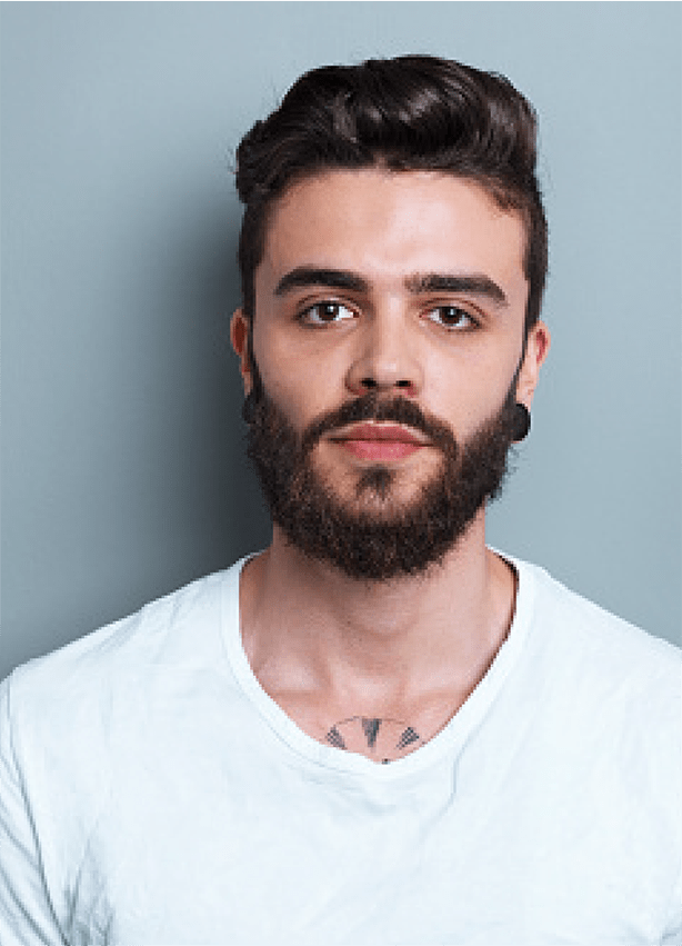 and image of the bust of a young man with brown hair and a beard wearing a white shirt. The beginning of a tattoo on his chest is visible at the top of his collar. He has a large black gage in each ear lobe.